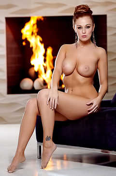 Leanna Decker exposing her big tits by a fireplace